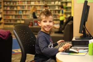 little boy at a computer smiling